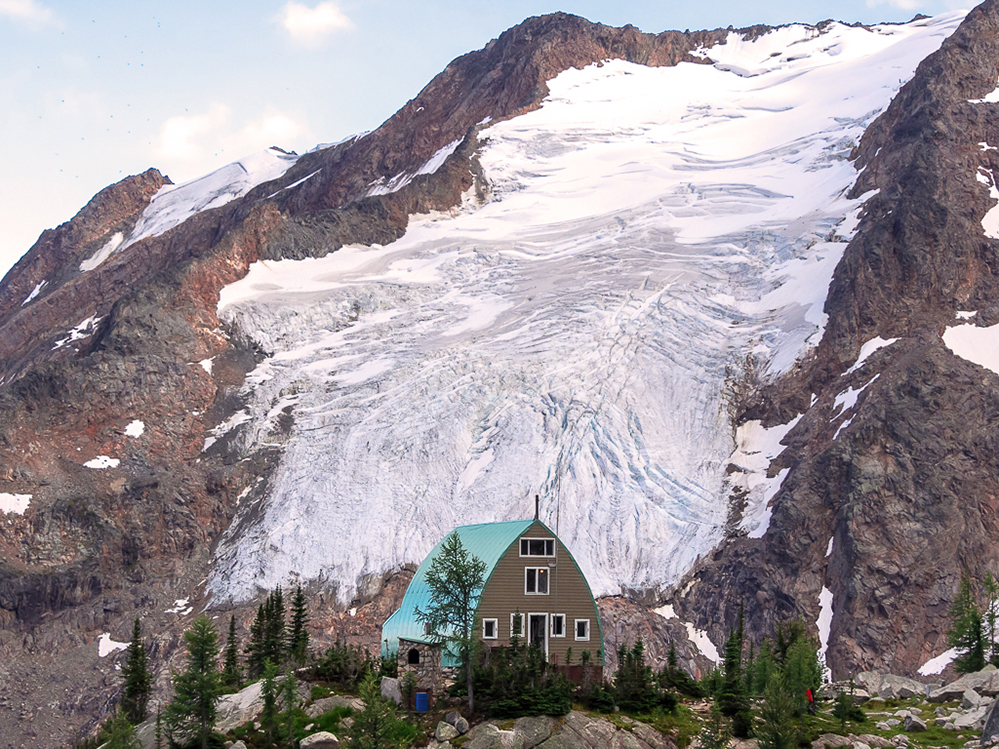 The Hut with its mint green arched roof, multiple windows and doorway framed in white sits surrounded by evergreen trees. A large glacier cascades down a steep slope behind the Hut.