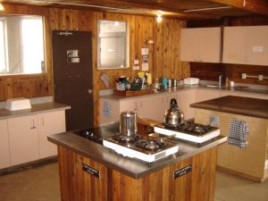 4 gas burners sit on one island countertop next to two additional burners. Another island is free for prep space and cupboards and countertops are located in the background against the wall.