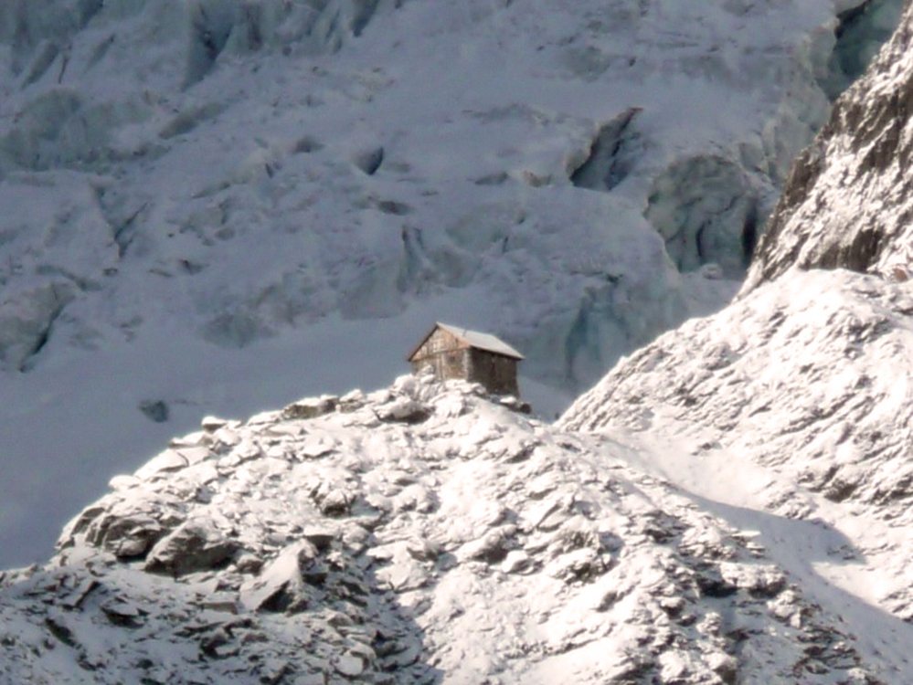 A stone shelter with an a-frame room sits on the top of a snow covered ridge and is bathed in sunlight. A large snow covered slope looms behind the shelter in the background.