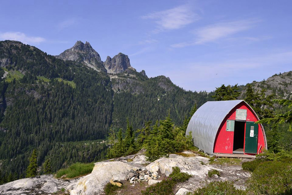 The photo was taken from an angle and the hut is located on the right hand-side with the front door open wide. The towering peaks across the valley from the hut stand out against the evergreen lined slopes.