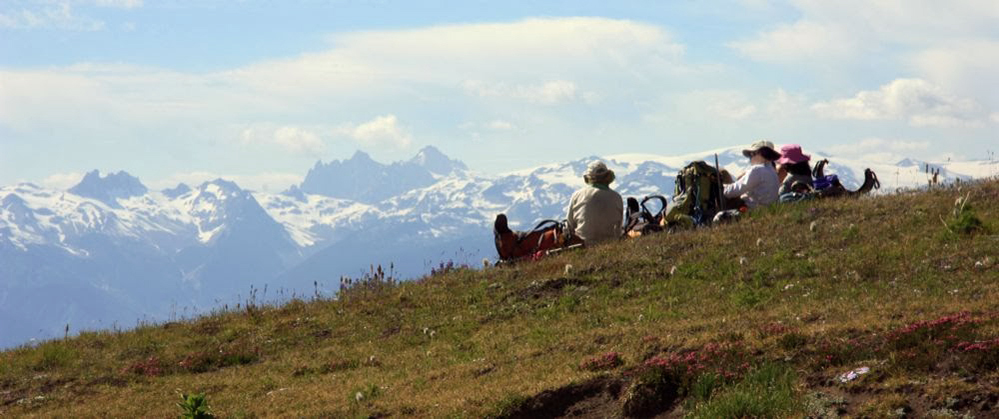 Three hikers sit near their backpacks all wearing sunhats looking out across at the distant mountain peaks. The peaks in the distance are covered in snow and clouds hang in the sky above them.