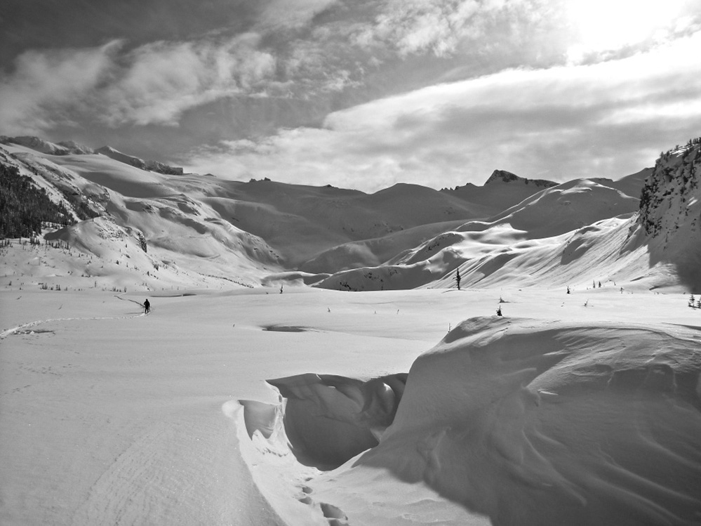 A black and white photograph of an alpine valley covered in snow with snow covered peaks in the background. A slight depression indicates where the Hut should be and a lone ski tourer is seen in the distance on the left.