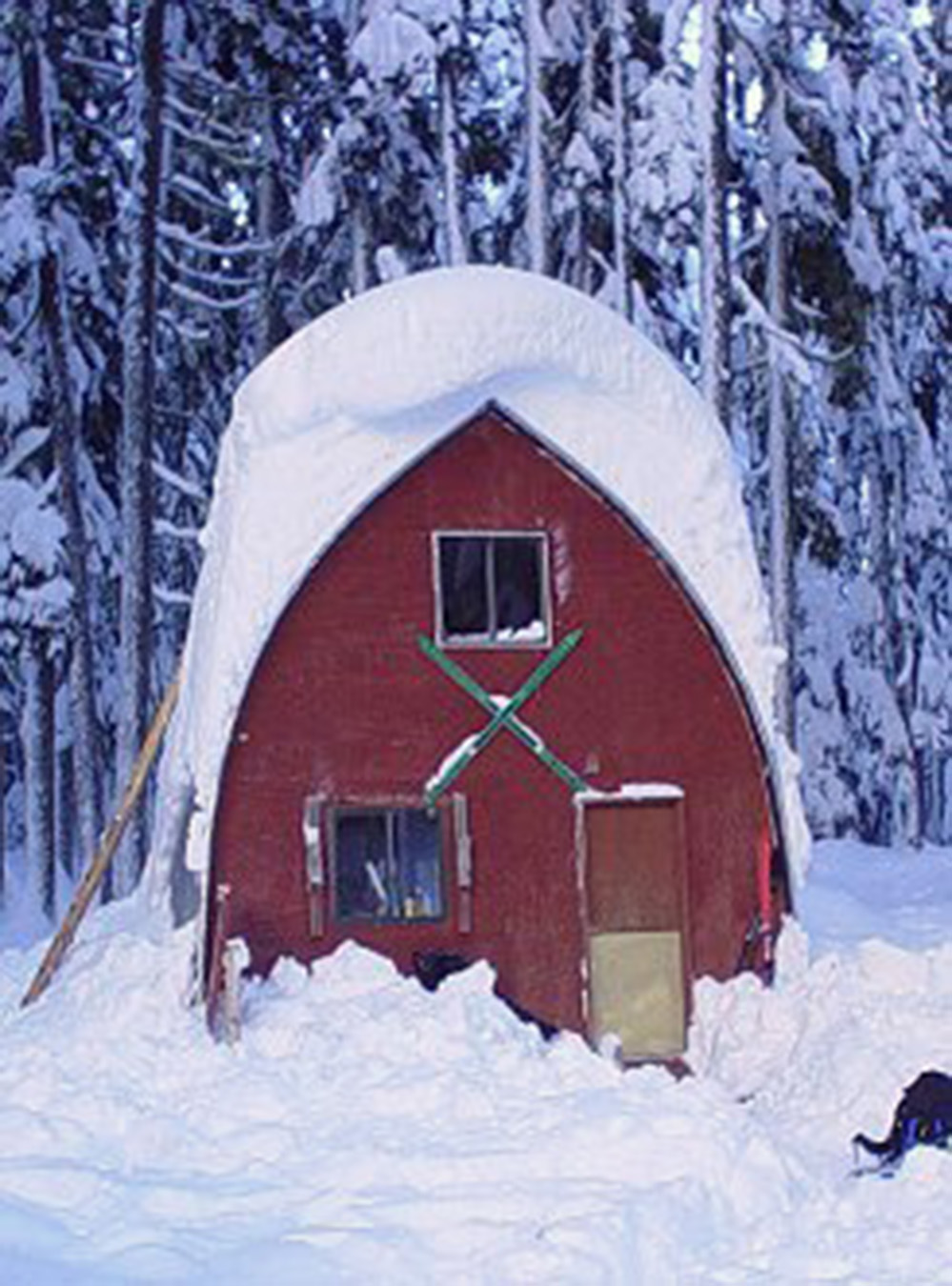 The front end wall of the gothic arch hut in the winter before maintenance was performed and the hut was repainted.