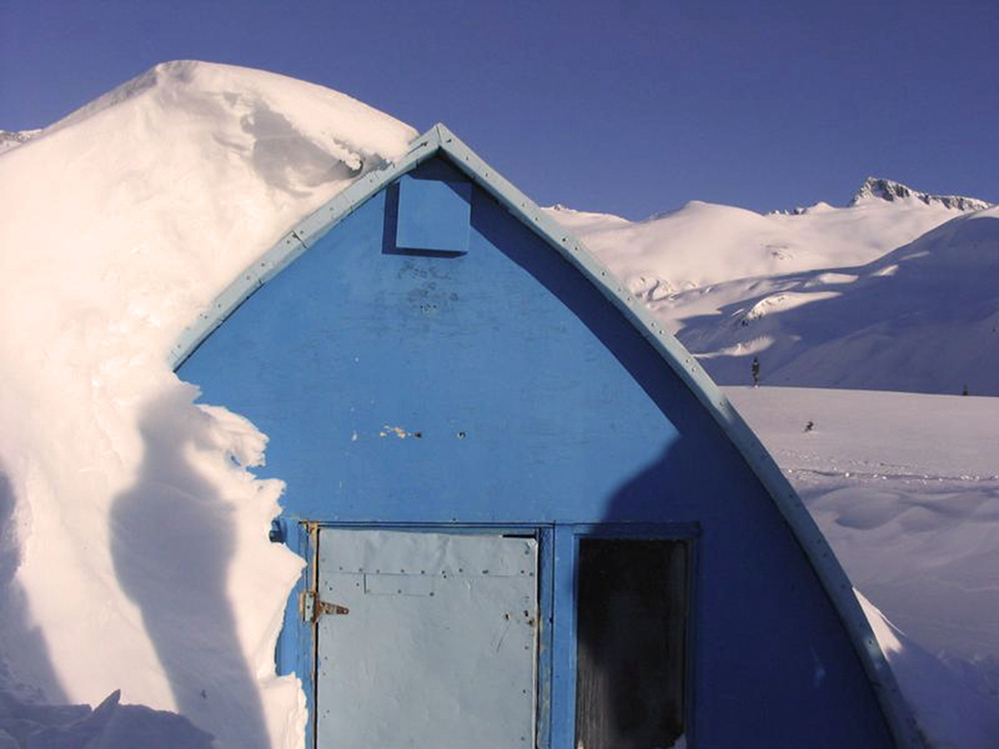 Blue front-wall of gothic arched hut nearly buried in snow, heaped up on one side and clear on the other. High snowy slopes and mountain peaks visible in background.
