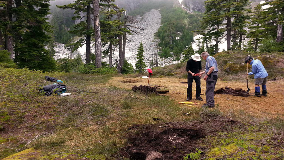 Two members appear to be discussing something near freshly dug holes for the Hut foundation.