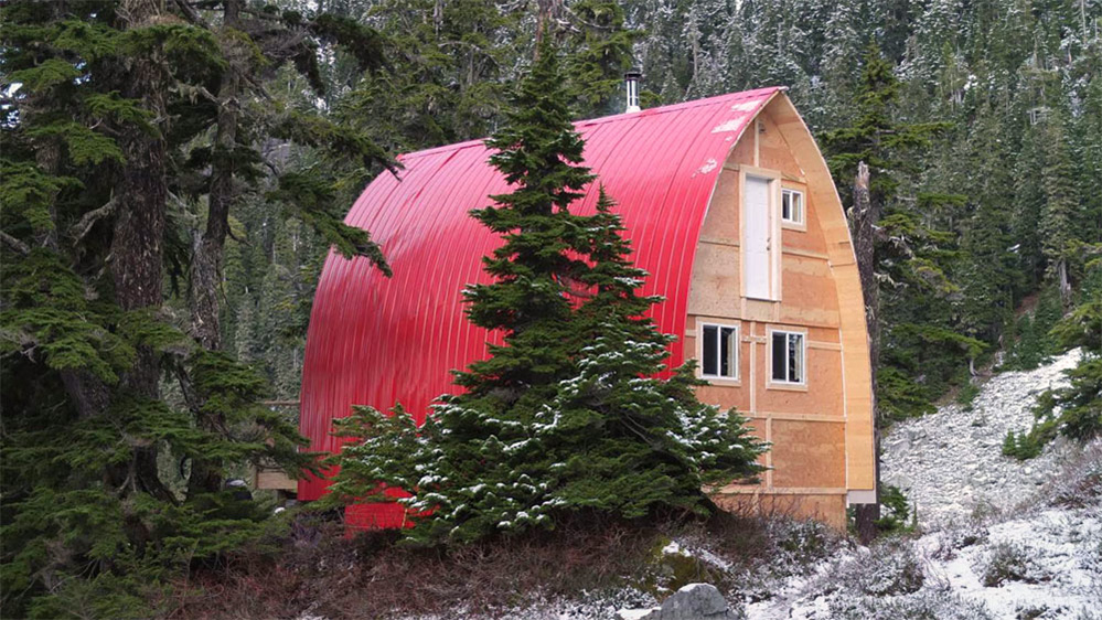 The bright red aluminum siding covering the roof of the arched Hut stands out against the dark green evergreen trees next to the hut. A light dusting of snow covers the ground and trees near the hut.