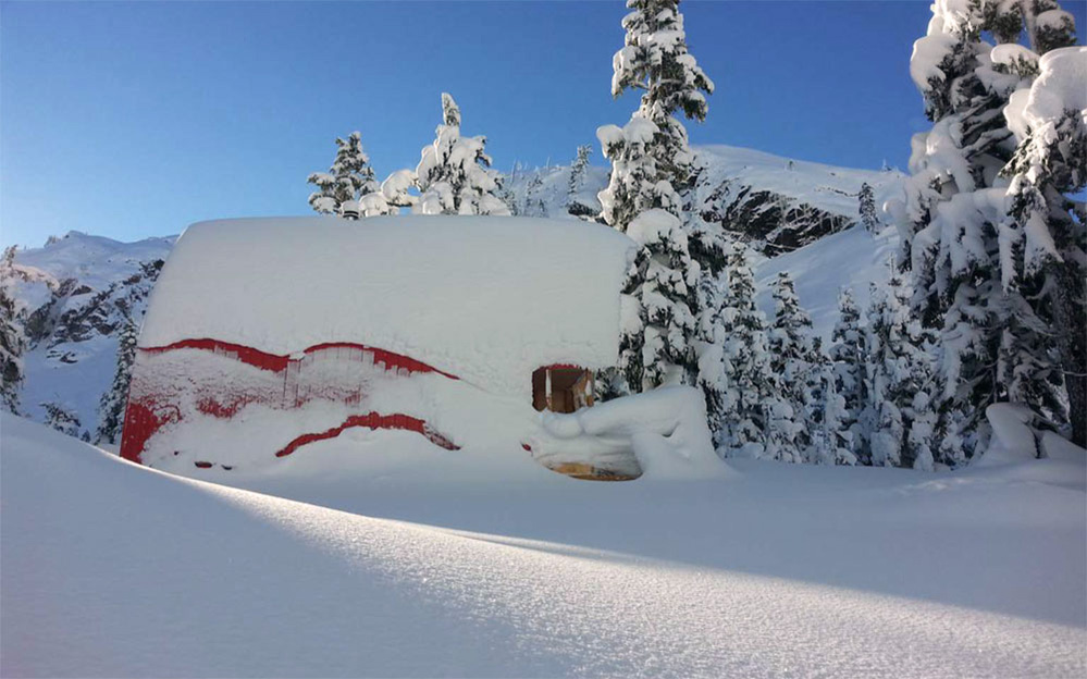 Deep snow surrounds the Hut and a portion of the red aluminum siding is uncovered. The winter sky is clear blue and snow covered evergreens are visible in the background.