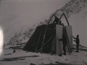 Snow covers the ground and the slope and three members of the construction crew attempt to assembly the Hut.