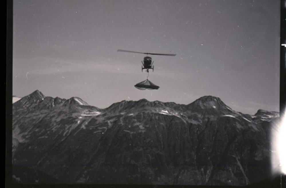 In the background, sits a range of mountains with small patches of snow. The flying helicopter is in the foreground carrying a load underneath the cockpit dangling from a cable.