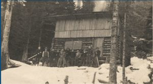 Black and white photograph, a Group of men stand in a line in front of the log cabin. Snow covers the ground around the cabin but the trees in the background are bare.