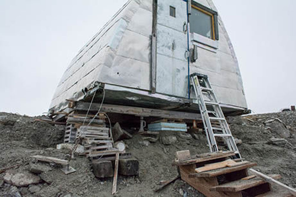 Aluminum siding wrapped Gothic arch hut supported by wood blocks because the earth below has been swept away. Wooden staircase can be seen in the foreground no longer attached to the hut.