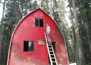 A man stands near the top of a retractable silver ladder holding a paintbrush and the painting is almost complete on the upper half of the Hut.