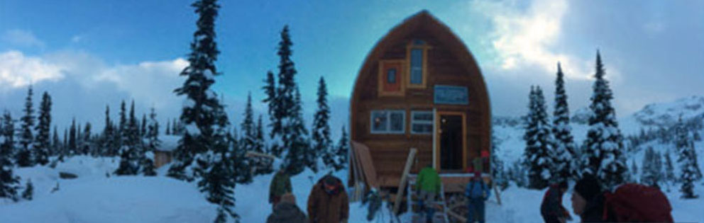 The Hut is under clear blue skies and several work-crew members are busy working out front in the snow.