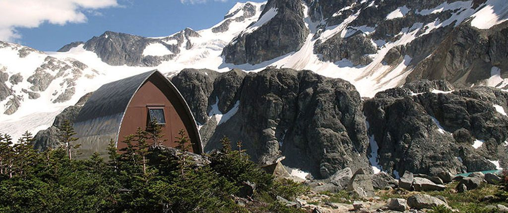 A Gothic arch hut surrounded by green evergreen trees sits in the sunshine with steep snow covered slopes in the background.