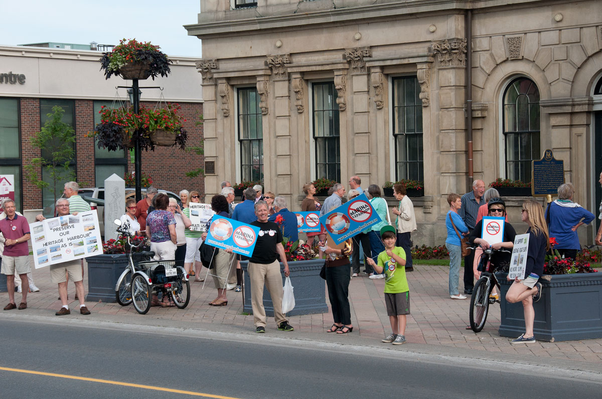 colour photograh of small crowd of adults and children waving placards on sidewalk in front of building
