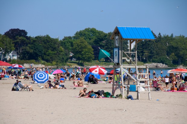 colour photograph of people lying on sandy beach with colourful umbrellas, life guard station unmanned