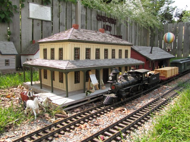 a colour photograph of 1/20 scale model of an antique black steam engine pulling a load of lumber in front of a two-story yellow station with a wood shake roof and a veranda. Two white horses with a cart and driver are near the tracks and a colourful hot air balloon flies in the background.