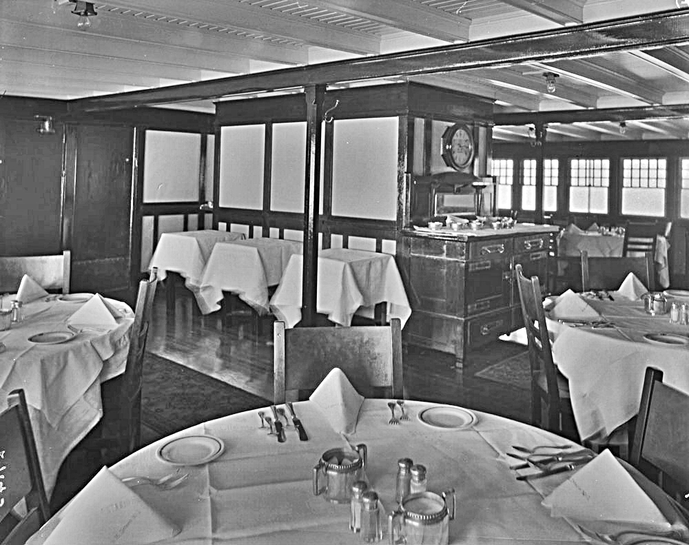 black & white photo of a sparse dining area with shiny wooden floor and carpet runners. Round tables are set with white table cloths, napkins, seven pieces of silverware and plates. Serving tables are in the middle background