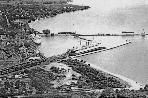 a black and white aerial photograph showing two ferries docked in Cobourg Harbour, one in the centre of the picture at a pier with its bow toward the lake and it's stern at the end of a railway line with railway cars on it, and the other at a dock along the shore. The picture includes the western extension of the harbour in the foreground and the beach in the distance.