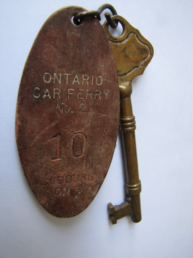 A bronze coloured skeleton type key attached by wire to a key fob made of brown material stamped with the text ONTARIO CAR FERRY No. 2 10 COBOURG ONT.