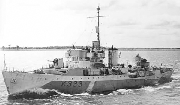 a black and white photograph of a Corvette style warship marked K333, sailing in from of a distant shoreline