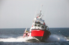 a colour photograph of a red and white vessel in open water heading toward the camera