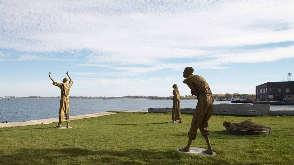 four bronze statues on a patch of green grass by the shore, standing at a distance from each other, turned towards the lake, one statue has its arms raised, one statue is a stooped, another is lying on the ground