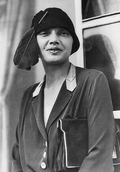 a black & white photo of a woman with full lips looking at the camera, with a purse under her left arm and a bowl shaped hat with large feather on her head