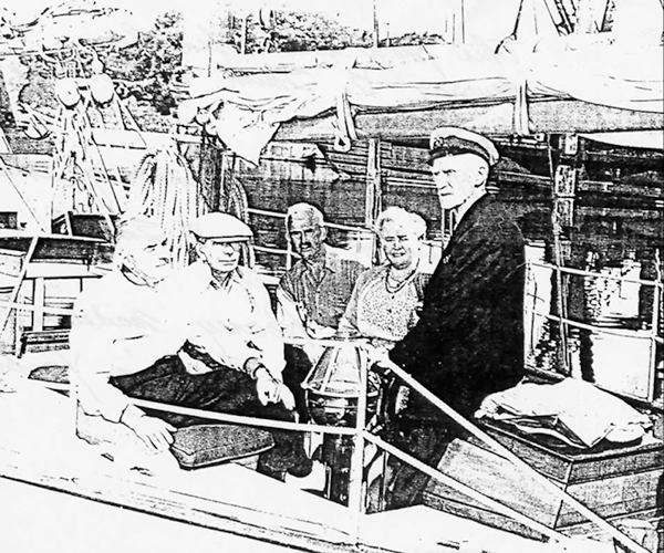 a poor quality photocopy of a photograph of five people in the stern of a boat, four seated and one standing wearing a captain's cap