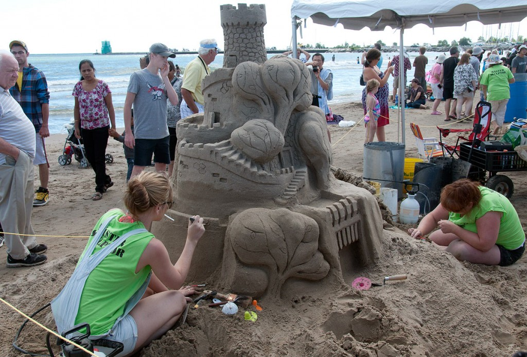 two female sand artists put the finishing touches to a large castle at blue water's edge, onlookers pause to admire the handiwork.