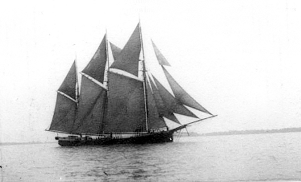 a black & white photograph of a sailing vessel with three masts and all sails up sailing by a distant shoreline