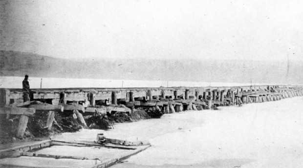 an old black and white photograph showing a rough wooden trestle bridge, nearby to the left and receding into the distance to the right over a lake which appears to be ice covered. A man sits on the bridge in the foreground and dimly in the distance is the other shore of the lake.