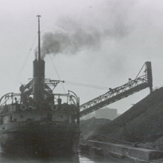 a dark black and white picture showing the stern view of a coal freighter on the left with a ramp carrying coal from the vessel and pouring it onto a huge coal pile to the right