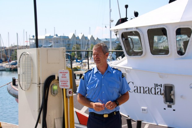 colour photograph of man dressed in summer blue uniform standing in front of a vessel marked Canada. Beside him is a large fuel pump