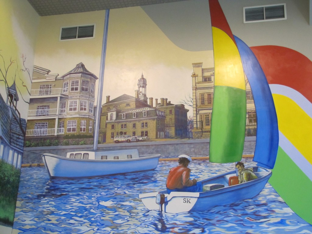 Photo en couleurs d'une peinture murale. En avant-plan à droite, dans l'eau bleue quelque peu agitée, il y a un petit bateau à moteur, deux voiles et deux passagers. Les initiales SK sont inscrites sur la poupe, une voile est rouge, jaune et verte tandis que l'autre est bleue. Un second bateau à voile, plus grand, et dont les voiles ne sont pas déployées, se trouve à gauche du premier. Il y a des immeubles à condominiums bruns et blancs sur la rive avec un espace entre eux permettant de voir le Victoria Hall surmonté par sa tour de l'horloge. Il y a deux grilles de ventilation complètement en haut de la murale.