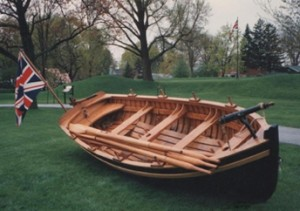 small wooden boat lying slightly tilted on green grass and flying Union Jack flag. It has four sets of oarlocks and four thwarts, two with holes for sail masts.