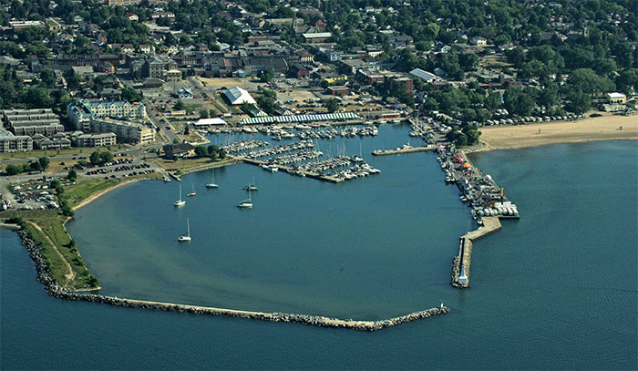 a colour aerial photograph of Cobourg Harbour showing a long breakwater at the bottom almost meeting the end of another pier to the right, leaving a narrow entrance into the harbour. The water is blue and inside the harbour sailboats are anchored or moored at a marina. On the shore from left to right are condominium buildings large tents erected for the Cobourg Festival and trailers parked in front of a sandy beach. In the distance are business buildings, residences and green trees.