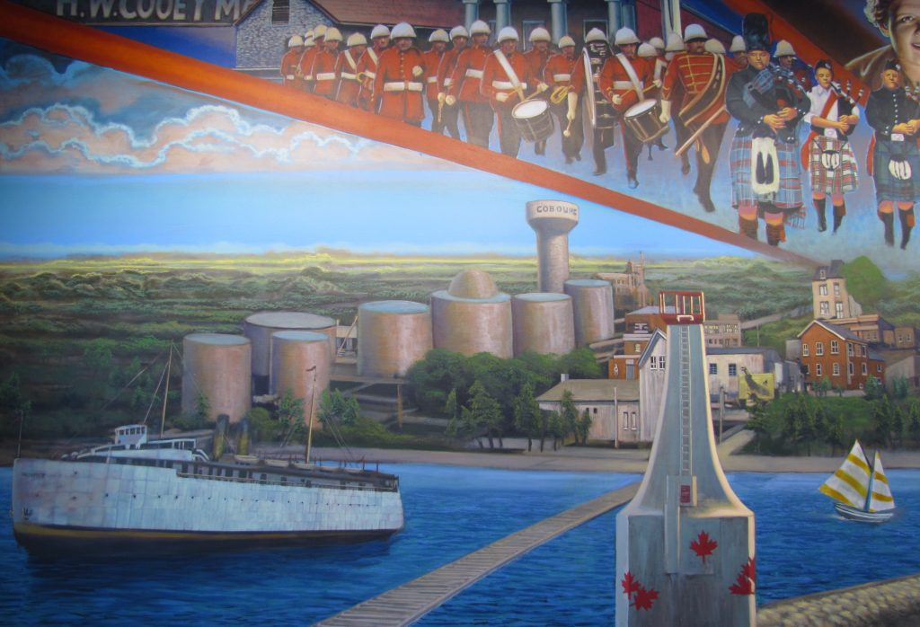 a colourful mural showing the current white Cobourg lighthouse to the right and a large white ferry to the left. On shore, in the distance to the left and centre, are seven large silver oil tanks and a water tower, and to the right beyond the lighthouse are a few businesses . Above them are depicted the red uniformed Cobourg Concert Band in marching formation and the Legion Bagpipe band in varied kilts