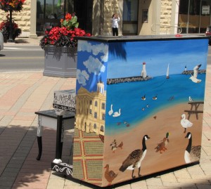 colour photograph of a street scene with the back and side of a piano in the foreground on a tiled sidewalk. On the side of the piano is a painting of Victoria Hall with a blue sky and on the back is a sunny harbour scene with a variety of ducks and swans in the foreground and the harbour entrance with lighthouse in the background. In front of the piano is a piano bench, at the near edge of the street is a large container of red flowers and across the street is a person taking a photograph.