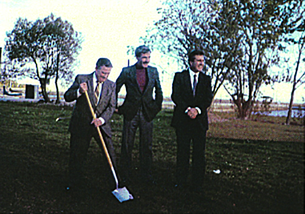 old colour photograph of three smiling men in suits posing on a patch of green grass with a shoreline in the background. The man to the left is inserting a shovel into the ground