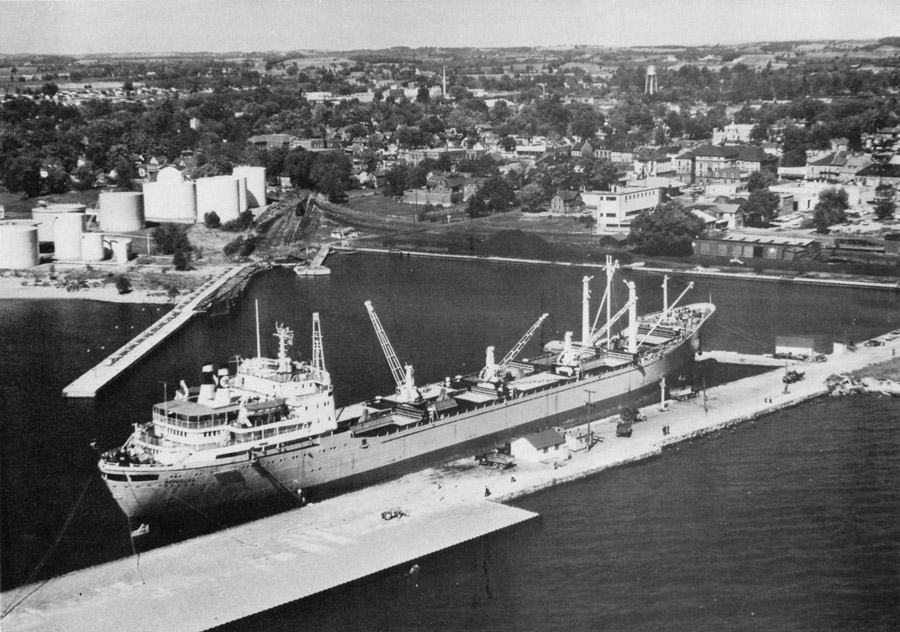 black and white photograph of a large freighter docked along a pier in the middle with a couple of cranes on board. A second pier leads back to oil tanks on shore to the left with piles of coal and a railway car along the shore between the two piers