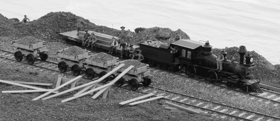 a black and white photograph of diorama reproducing a rare photograph. in the foreground planks of lumber lean against one of four ore cars on rails. Beyond is a steam engine with a tender full of lumber and a flatbed. Scattered on and around these are a dozen workers posing for the picture.