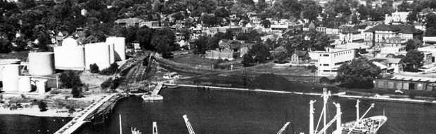 a black and white photo of an industrial harbourfront with white oil tanks to the left, railway lines and piles of coal in the middle and a boxcar to the right. In the right distance is Victoria Hall.