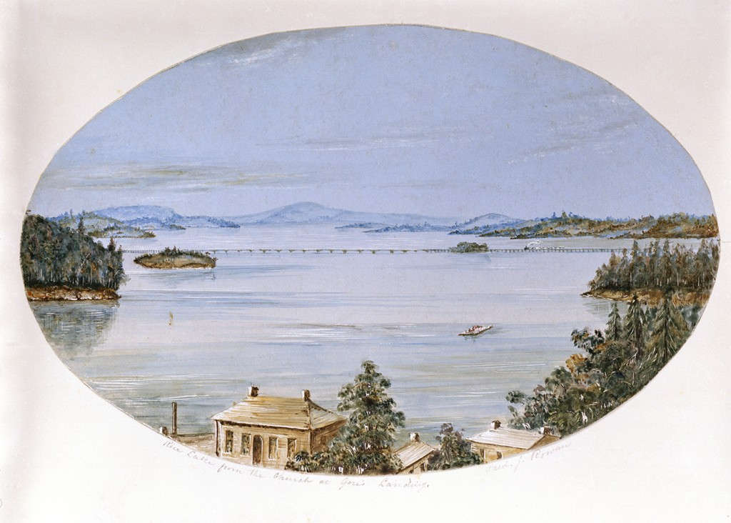 photograph of a watercolour painting showing roofs of houses in the foreground, hills in the distance and cam water in between. In the middle distance a long bridge is being crossed by a steam engine with an indeterminate number of cars. Nearer by is a barge