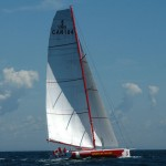 a colour photograph of a sleek red and white hulled sailboat on dark blue water with two white sails against a light blue sky. flying a Canadian flag