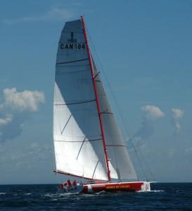 Une photo en couleurs d'un voilier aux lignes pures, avec une coque rouge et blanche, naviguant sur l'eau d'un bleu foncé, ses deux voiles blanches contrastant avec le ciel bleu. Un drapeau du Canada flotte à l'arrière du bateau.