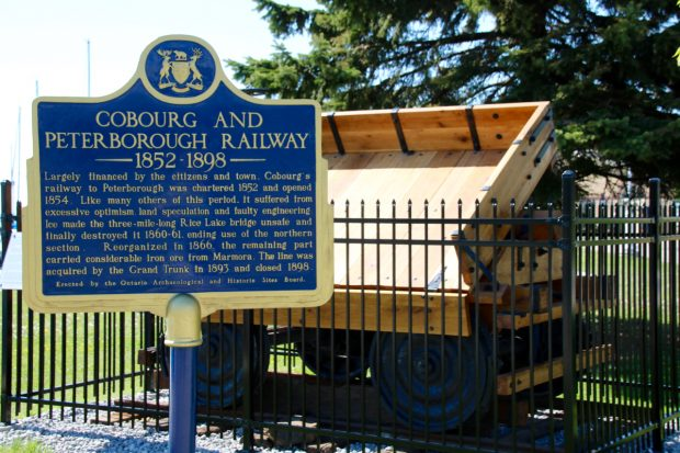 blue Province of Ontario history plaque tells the story of the Cobourg and Peterborough Railway in front of a full-size replica of an 1867 ore car, not far from where the original was built