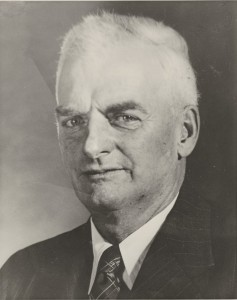 Photograph of Mr. Frank Bickle facing camera with short white hair, white shirt, jacket and tie