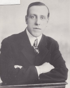 W.H. Bunting has his arms folded in this photograph. He looks serious and he is wearing a dark suit, light shirt and tie.