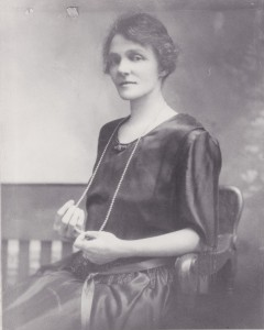 Violet Guymer as a young woman posing for a portrait. She is wearing a dark dress and has a string of pearls that extends to her lap.